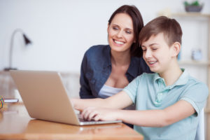 Single Mom and child looking at laptop laughing