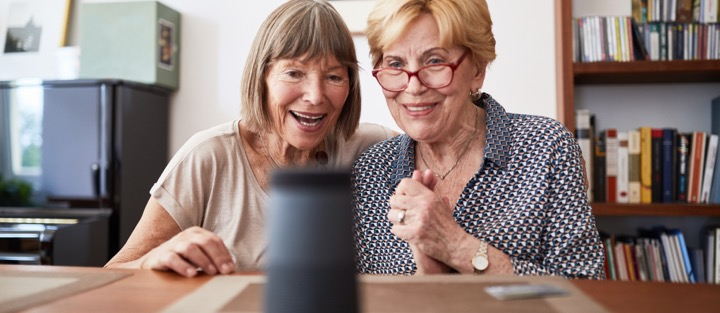 Two older women check out an Alexa assistant device.